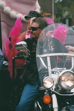 Man and Woman on Motorcycle in the Parade