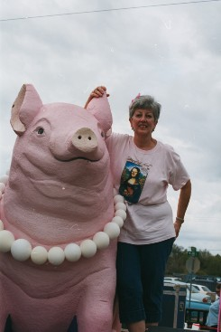 Woman Posing Next to Pig Statue